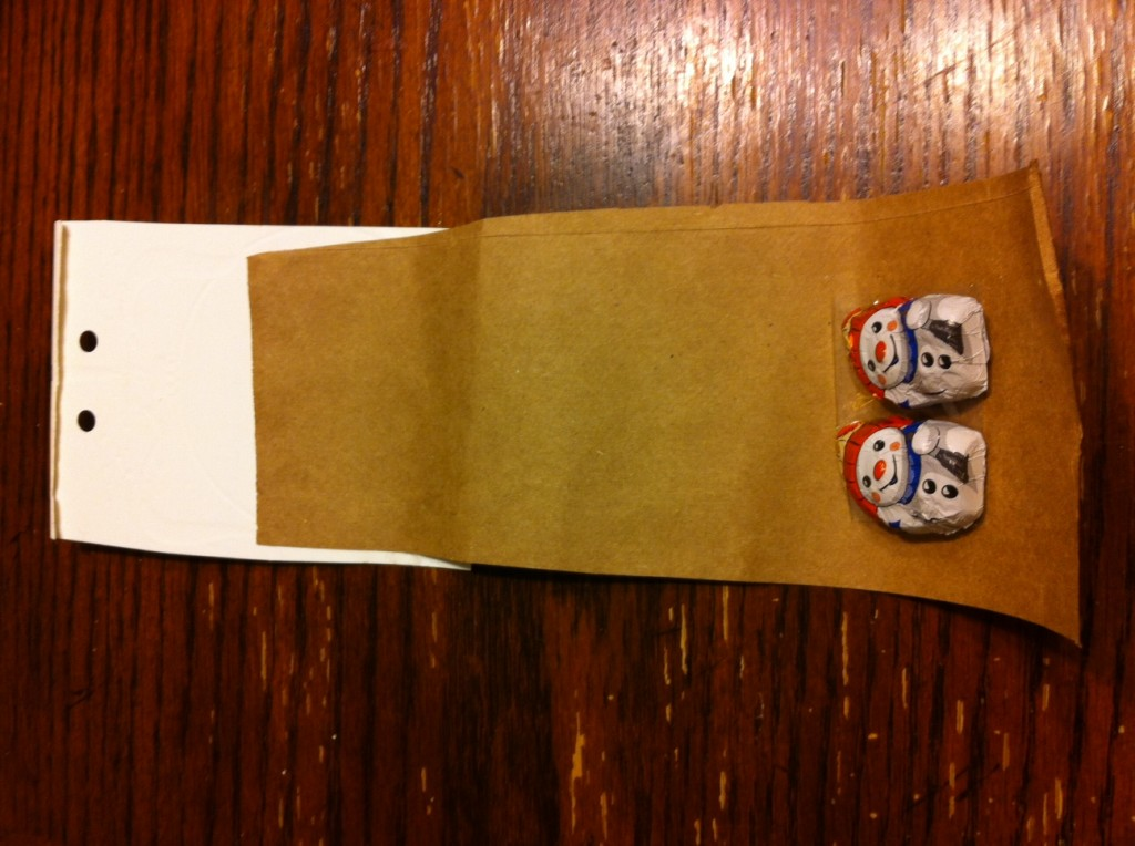 Christmas card with brown paper attached, candy taped to bottom